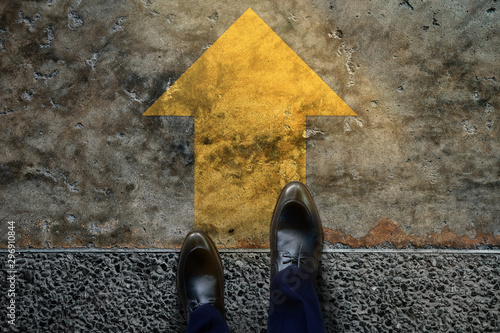 Obraz Start and Challenge Concept. a Business Man on Formal Shoes Steps to Follow a Yellow Arrow, Get Ready to Moving Forward or take a Chance to Success. Top View - fototapety do salonu