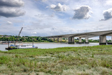 Distant View Of A Major Motorway Crossing, Spanning The River Medway, The Foreground Shows A Moored Up Vessel By The Marshes Banks Of The River.