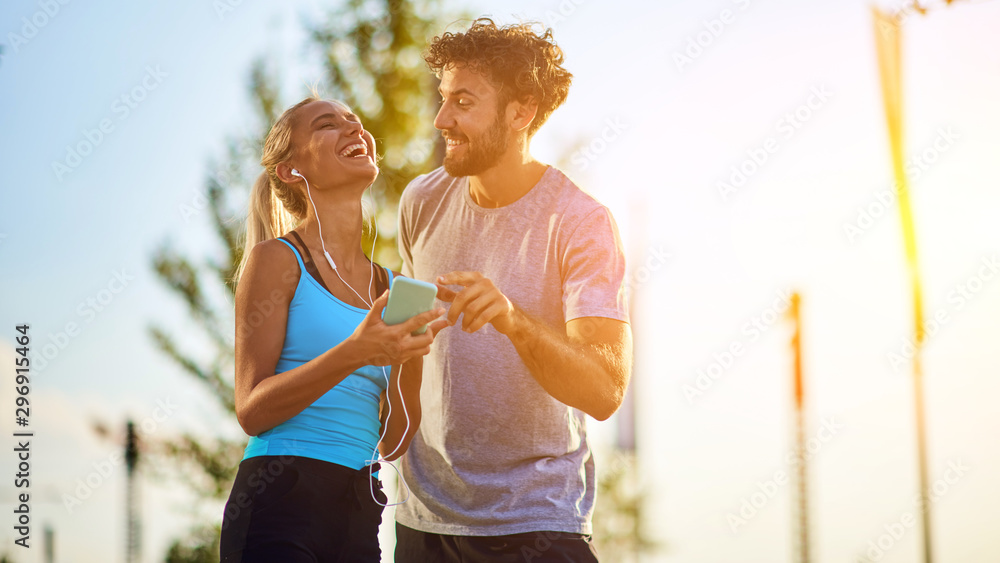 Fototapeta Modern woman and man jogging / exercising in urban surroundings and using cellphone at a pause / break.