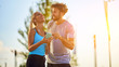 Modern woman and man jogging / exercising in urban surroundings and using cellphone at a pause / break.