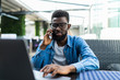 Portrait of african man talking on phone with laptop in cafe
