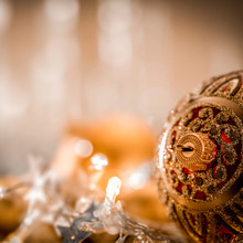 Christmas Decorations In Bright Gold Shiny Colors With Christmas Lights With Blurred Background.