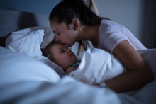 Mother Kissing Her Sleeping Daughter On Bed