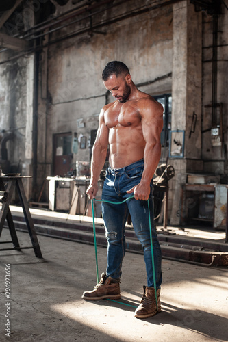 Fototapeta  Muscled half naked man at work in an old factory.