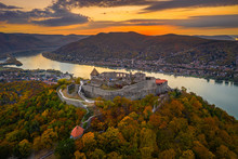 Visegrad, Hungary - Aerial Drone View Of The Beautiful High Castle Of Visegrad With Autumn Foliage And Trees. Dunakanyar And Golden Sunset At Background