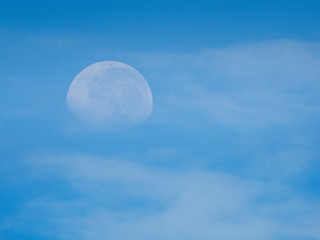 view morning of full moon 70% falling around with white clouds and blue sky background.