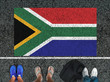 canvas print picture - people legs are standing on asphalt road next to flag of South Africa and border