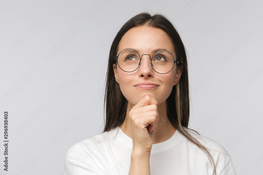 Fototapeta Portrait of young woman with dreamy cheerful expression, thinking, wearing eyeglasses, isolated on gray background - obraz na płótnie