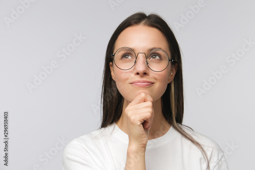 Fototapeta Portrait of young woman with dreamy cheerful expression, thinking, wearing eyeglasses, isolated on gray background obraz na płótnie