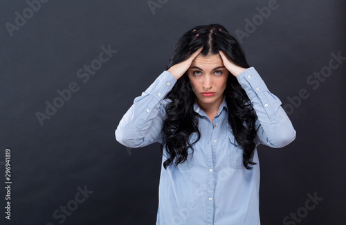 Young woman suffering from headache on a black background Wallpaper Mural