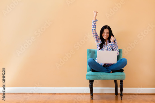 Fotografía  Young woman with a laptop computer with successful pose sitting in a chair