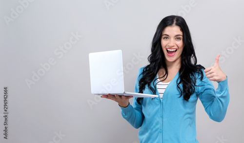 Fotografie, Tablou  Young woman with a laptop computer giving thumb up on a gray background