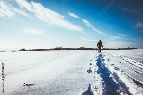 Fotomural  man walking in snow footprints