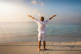 Fototapeta Big Ben - Mann in weißer Sommerkleidung und mit ausgestreckten Armen steht am tropisch Strand und genießt den Sonnenuntergang