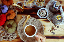 Woman Hand Hold Coffee Cup On Autumn Background With Decor Seasonal Ornament Table
