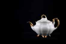Vintage Porcelain White Teapot With Gilding On A Black Background With Copy Space