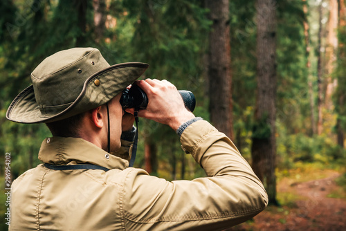 Fotomural A man in a hat and uniform green and beige holds binoculars and looks into the d