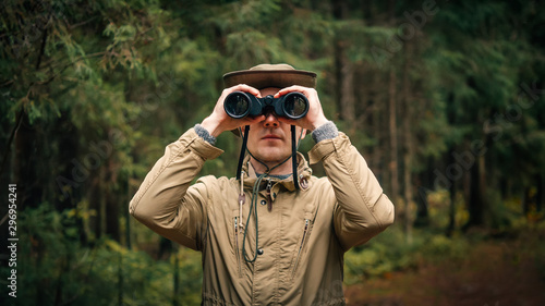 Fotografía A man in a hat and uniform green and beige holds binoculars and looks into the d