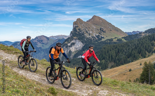 three happy senior adults, riding their mountain bikes in the autumnal atmosphere of the Bregenz Wald mountains near Mellau, Vorarlberg, Austria