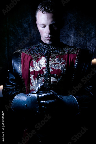 Portrait of handsome medieval knight in suit of armour with beard looking down i Wallpaper Mural
