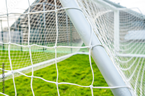 Obraz Shallow focus of a newly delivered football goal located in a village park. Detail of the white netting and knots are visible. - fototapety do salonu