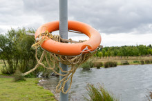Orange Rescue Flotation Ring Seen Located By The Water's Edge Of A Flooded Inland Quarry. Seen Hooked Over A Long Pole, In Case Of Emergency.