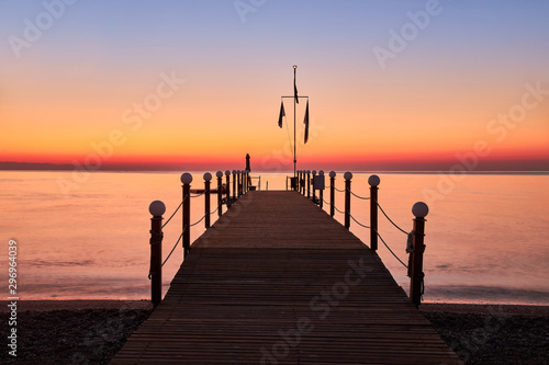 Foto auf Gartenposter Koralle Dawn view of the warm calm sea and a wooden pontoon