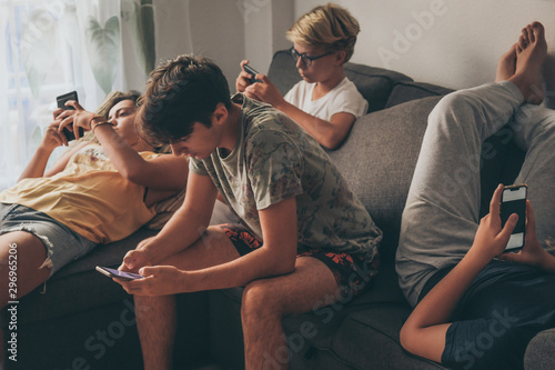 Photo Group of teenager using smartphone sitting on a sofa at home