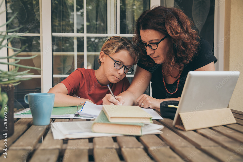 Fototapeta Young student doing homework at home with school books, newspaper and digital pad helped by his mother. Mum writing on the copybook teaching his son. Education, family lifestyle, homeschooling concept