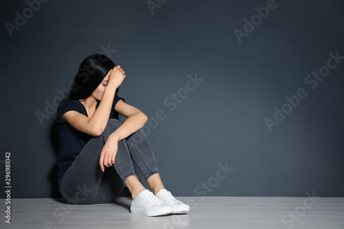 Valokuva  Upset young woman sitting on floor near grey wall. Space for text