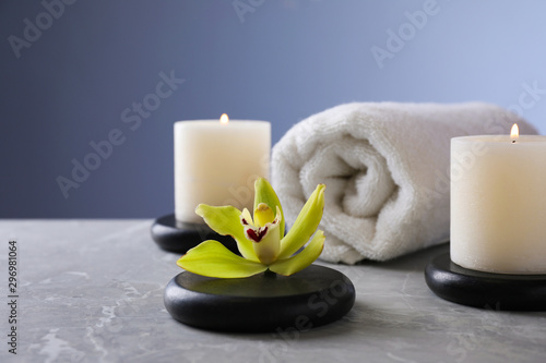 Fotografia  Spa stones with exotic flower and burning candles on grey table, space for text