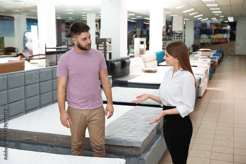 Pinturas sobre lienzo  Young saleswoman helping customer to choose new modern orthopedic mattress in st