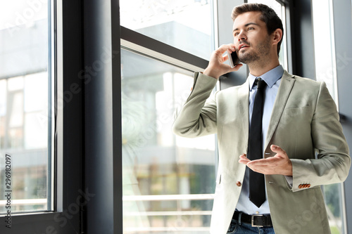 Fototapety, obrazy: Male business trainer talking on phone in office