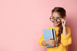 canvas print picture - Cute little girl with glasses and books on pink background, space for text. Reading concept