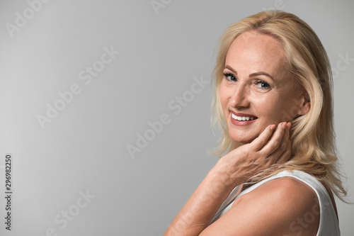 Carta da parati  Portrait of beautiful mature woman with perfect skin on grey background
