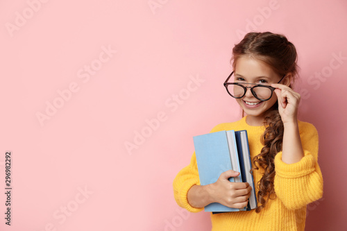 Fotografiet Cute little girl with glasses and books on pink background, space for text