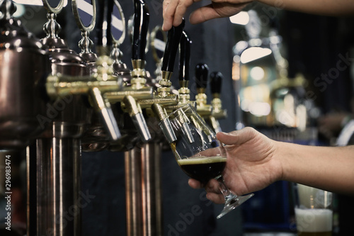 Photo sur Toile Alcool Bartender pouring beer into glass in pub, closeup