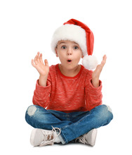 Cute Little Child Wearing Santa Hat On White Background. Christmas Holiday