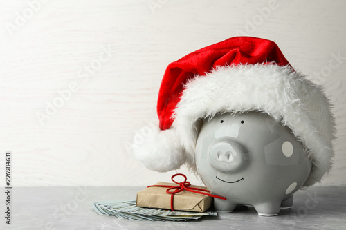 Fototapeta Piggy bank with Santa hat, gift box and dollar banknotes on grey table. Space for text obraz