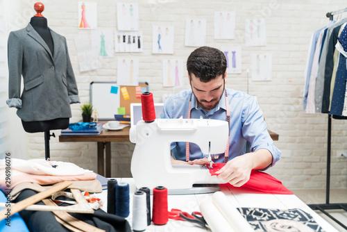 Obraz na plátně  Tailor stitching cloth on sewing machine at workbench