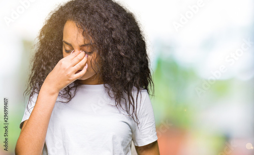 Fotografiet Young beautiful girl with curly hair wearing casual white t-shirt tired rubbing nose and eyes feeling fatigue and headache