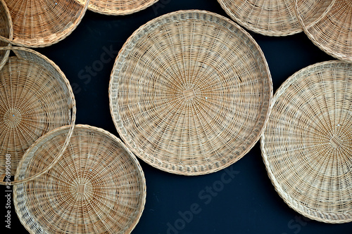 Rattan sift and basket hanging on the black wall Wallpaper Mural