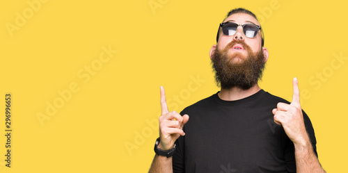 Photo  Young hipster man wearing sunglasses amazed and surprised looking up and pointing with fingers and raised arms