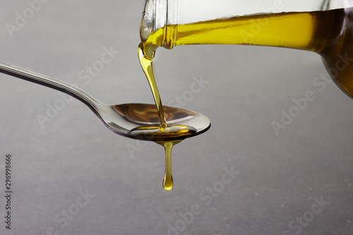 pouring olive oil from glass bottle on grey background