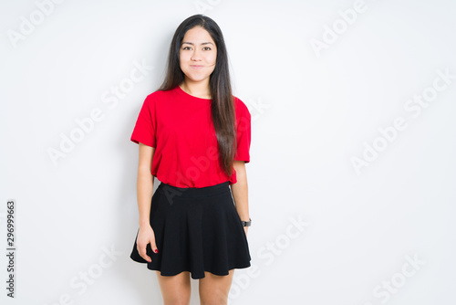 Beautiful brunette woman wearing red t-shirt and skirt over isolated background puffing cheeks with funny face Canvas Print