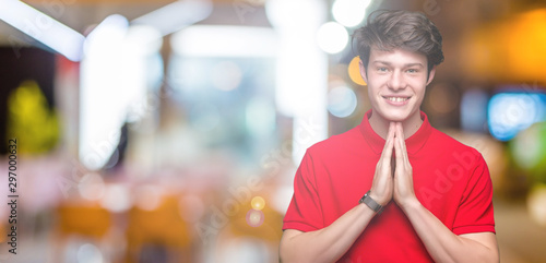 Fotografie, Tablou  Young handsome man wearing red t-shirt over isolated background praying with hands together asking for forgiveness smiling confident