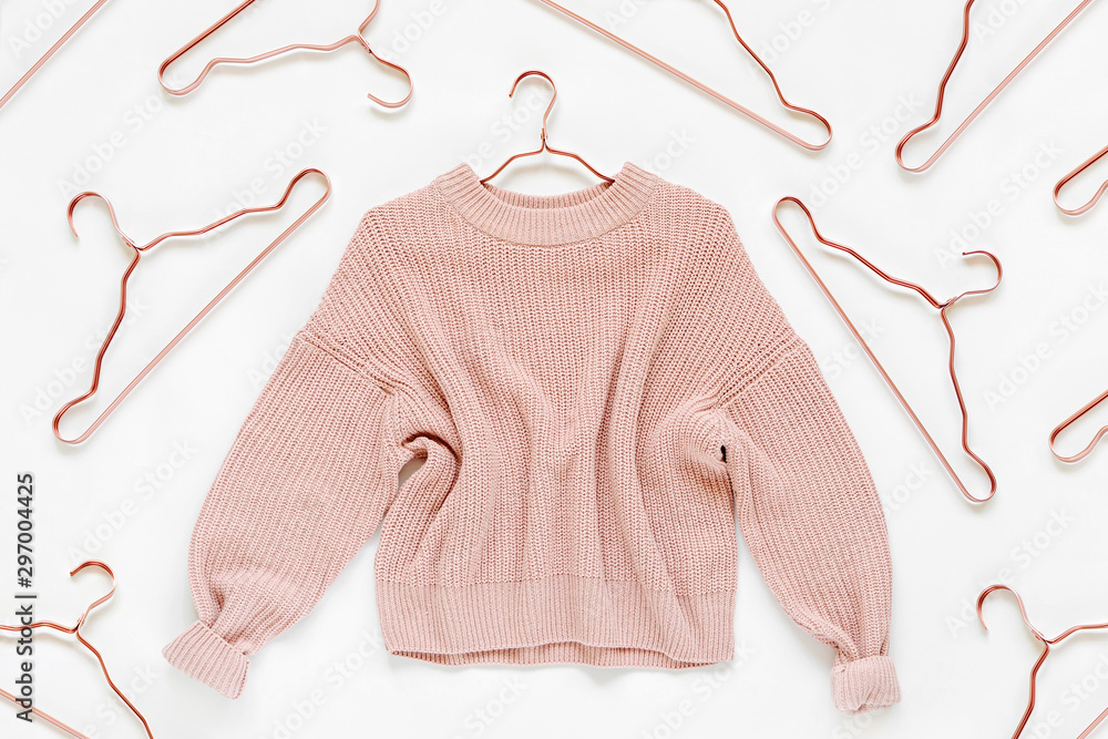 Fototapety, obrazy: Pale pink knitted sweater with metallic hangers on white background. Autumn and winter clothes. Store, sale, fashion concept.