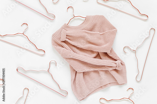Fototapeta Pale pink knitted sweater with metallic hangers on white background