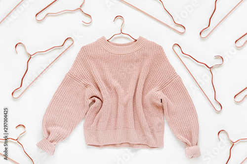 Obraz Pale pink knitted sweater with metallic hangers on white background. Autumn and winter clothes. Store, sale, fashion concept. - fototapety do salonu