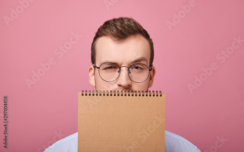 Fotografering  A young student in a gently blue shirt with glasses covered his face with a brown loose-leaf notebook and looks into the frame, is on a pink background